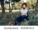 Small photo of Young poet writing in his sketchbook in forest. Attractive man have rest while walking at nature, copy space for text. Idea, inspiration, afflatus concept