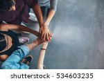 Stock photo top view image of group of young people putting their hands together friends with stack of hands 534603235