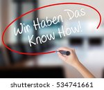 Small photo of Woman Hand Writing Wir Haben Das Know How! (We Have the Know-How in German) with a marker over transparent board. Isolated on Office. Business concept. Stock Photo