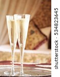 Small photo of Two champagne glasses with oriental canopy bed at the background. Silver tray. Romantic concept. Valentines background. Arabian nights ambiance. Vertical, close up