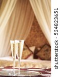 Small photo of Two champagne glasses with oriental canopy bed at the background. Silver tray. Romantic concept. Valentines background. Arabian nights ambiance. Vertical, general view
