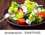 Small photo of Greek salad plate with lettuce, tomatoes, feta cheese, cucumbers, black olives, purple onion on dark wooden background close up. Healthy eating. Delicious traditional food