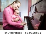 Happy Mother And Baby Daughter Are Playing Piano At Home - stock photo