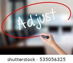 Small photo of Woman Hand Writing Adjust with a marker over transparent board. Isolated on Office. Business concept. Stock Photo