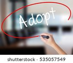 Small photo of Woman Hand Writing Adopt with a marker over transparent board. Isolated on Office. Business concept. Stock Photo
