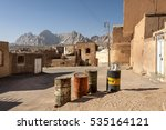 Small photo of Iran, Anarak - October 17, 2016: Four old oil drums in the center of the old desert village with blue sky and a chain of mountains in the background.