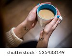 Small photo of drinking coffee to warm your hands mug, bright color nails, a tattoo on the wrist tattoo in the form of signs of alteration