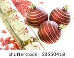 an arrangement of seasonal decorations, baubles, confetti shapes and a christmas cracker - stock photo