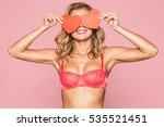 Stock photo beautiful blonde woman in lingerie with cards in the shape of a red heart in his hands on a pink 535521451