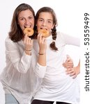 Portrait of a mother and her daughter eating doughnuts - stock photo