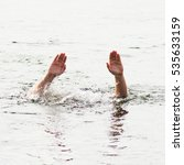Small photo of man drowning in the sea and waving hand for help