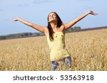 Image of joyful girl with stretched arms standing in the middle of rye field