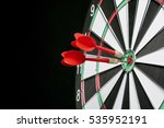 Small photo of Center target of darts isolated on a black background