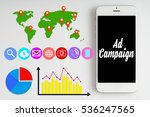 """Small photo of """"Ad campaign"""" words on smartphone with social media icon, graph, pie chart, map and location services with white background - business, finance and copy space concept"""