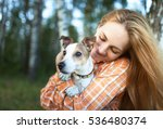 Stock photo young girl in square patternt shirt with fair hair hugging her dog 536480374