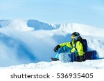 Vertical full length shot of a female snowboarder wearing yellow pants blue jacket yellow helmet and ski goggles posing with her snowboard at the mountains extreme sports recreation free ride concept