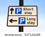 Small photo of Directional sign for a long stay and short stay carpark against a partly cloudy sky background