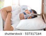 Small photo of Happy and healthy senior man wearing Cpap mask sleeping smoothly all night long on his left side cross arms without snoring.Obstructive sleep apnea therapy.