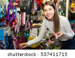Stock photo ordinary female teenager customer buying accessories for pet in shop 537411715