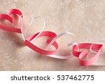 Small photo of Dainty chain of alternating red and white paper hearts symbolic of love and romance on neutral floral wallpaper background with copy space for your Valentines message to a sweetheart