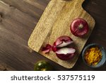 Small photo of Red bisect onion, tomato, turmeric on wooden table. Close-up from above.