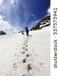 Small photo of Dog and hikers in snow mountain at sun day. Turkey, Kachkar, highest part of Pontic Mountains. Wide angle view