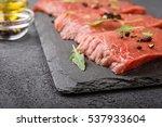 raw  beef steak on a dark ... | Shutterstock . vector #537933604