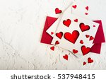 Small photo of Valentine day. Red hearts and envelopes on white concrete background. Free space for your text.