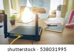 Small photo of closeup of a wireless router and a man using smartphone on living room at home ofiice