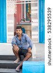 Small photo of KOCHI, INDIA - DECEMBER 16, 2016: Indian worker sitting on the steps of a religious blue alter with a water bottle