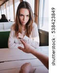 Small photo of Vertical image of young touchy woman sitting by the table with arms crossed in cafe with her man. First-person view