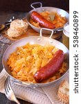 Small photo of Braised sauerkraut and smoked sausages in two vintage metal bowl, beer and bread on wooden background