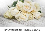 Stock photo white roses on a old white wooden table 538761649