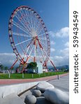 Small photo of Ferris wheel on the Batumi seaside on sunny day with beautiful stone-shaped benches,Georgia,Adzharia