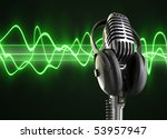 A microphone with headphones on top woth a audio wave background. - stock photo