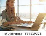 Small photo of Woman freelancer female hands with pen writing on notebook at home or office