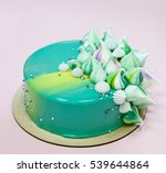 Small photo of Trendy mousse cake decorated with mint green mirror glaze and meringue kisses. Pink background