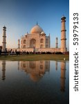 The majestic Taj Mahal is beautifully reflected in a puddle of water. - stock photo