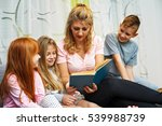 mother reading a book to her... | Shutterstock . vector #539988739
