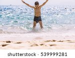 Boy Jumping In Sea Waves. Jump...