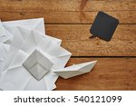 Paper Boat On Pile Of Folded...