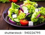 Small photo of Greek salad plate with lettuce, tomatoes, feta cheese, cucumbers, black olives, purple onion on dark wooden background close up. Healthy eating. Delicious traditional food. Clean eating.