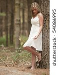 Small photo of beautiful teenage girl wearing white flowy dress in forest