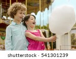 Small photo of Children are amazed with the size of cotton candy. Two cute siblings look at the dessert with amazement, while little girl opened her mouth.