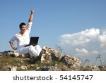 Young man using his laptop, sitting on the  rocky - stock photo