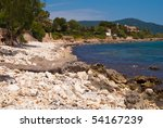 Small photo of White pebble on the beach of Mediterranean Sea. Hotels and residential area in Cala Bona suburbs, Majorca island, Spain