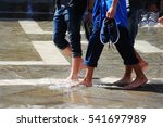 Small photo of Young men at high water Acqua alta in Venice, Italy