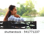 woman sitting on a park bench... | Shutterstock . vector #541771237