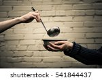 Small photo of Homeless. In the hands of one man metal plate. In the hand of another person ladle.