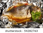 fried fish with tomato in foil - stock photo